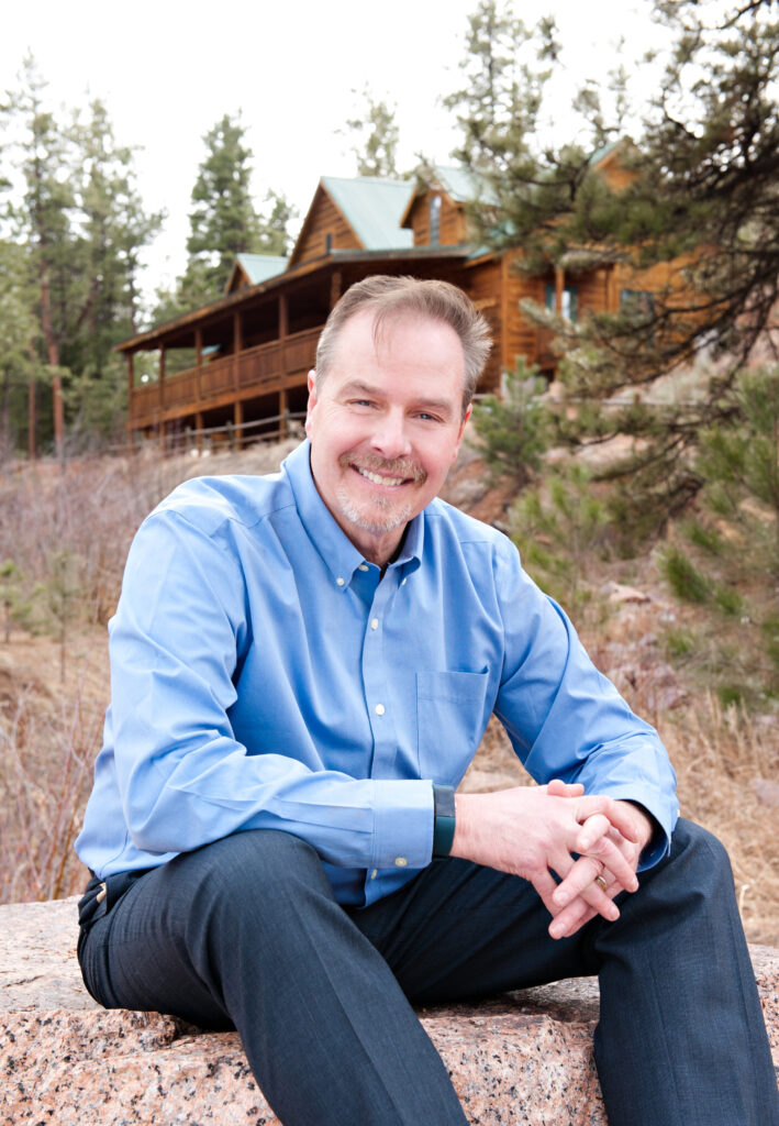 Rob Henderson pictured outdoors in front of cabin in mountains