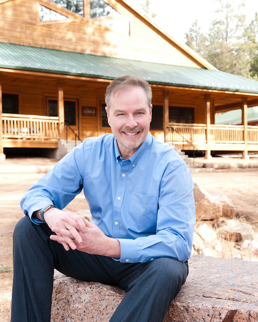 Rob Henderson pictured outdoors in front of cabin